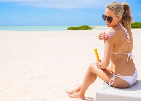 Eine Frau sitzt am Strand und gibt Sonnenschutz auf Ihre Schulter