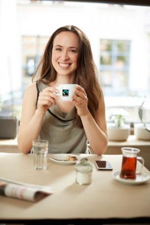 Eine Frau trinkt Kaffee aus einer Tasse mit Fairtrade Logo