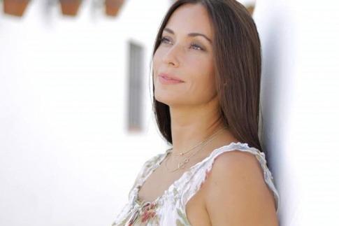 Eine Frau über 40 mit schönem Augen-Make-up lehnt an einer Wand