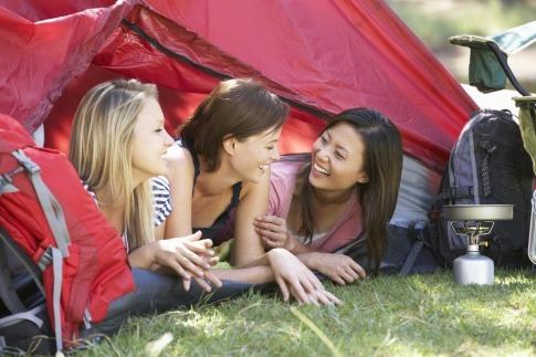 Drei Frauen liegen bei einem Frauencamp in einem Zelt