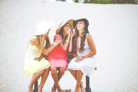 Drei Freundinnen sitzen in Stühlen und lachen miteinander