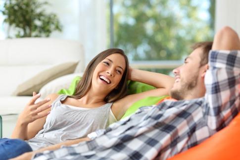 Ein frisch verliebtes Paar sitzt lachend auf dem Sofa