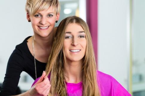 Eine Friseurin hält die langen Haare einer Kundin