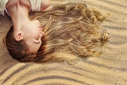 Eine Frau liegt mit ihrer Frisur am Sandstrand im Sommer