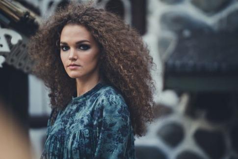 Eine Frau trägt als Trendfrisur 2021 naturkrause Haare