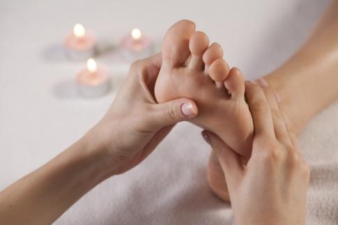 Ein Fuß wird auf den Fußreflexzonen massiert