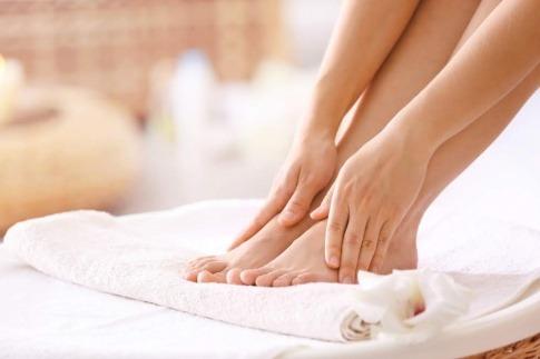 Eine Frau hält ihre Füße ohne Nagelpilz