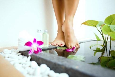 Zwei Füße gehen am Rand eines Bades