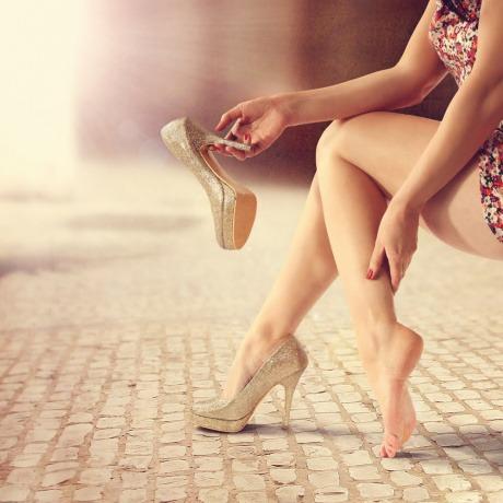 Eine Frau hat einen Schuh in der Hand und greift auf den Fuß