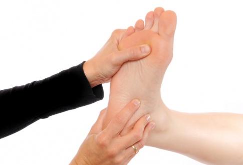 Eine Hand führt eine Fußreflexzonenmassage durch