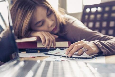 Eine Frau liegt Schreibtisch über Büchern und Unterlagen