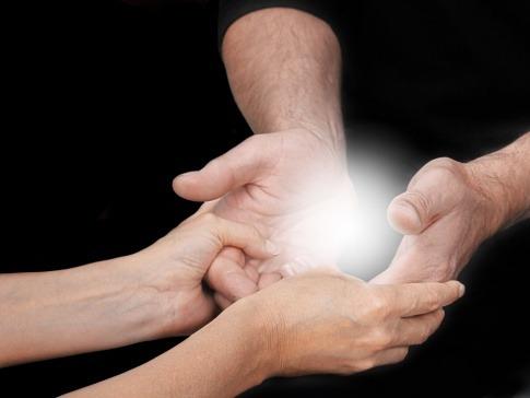 Zwei Paar Hände die Energie übertragen