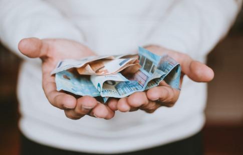 In einer Hand liegen Geldscheine