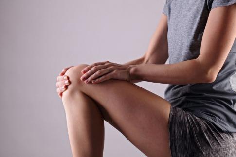 Frau greift sich an ihr Knie.