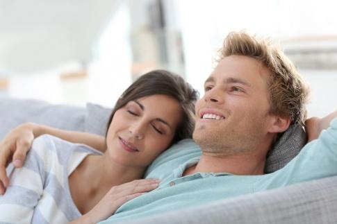 Ein Paar sitzt auf einer Couch und scheinen sich geliebt zu fühlen