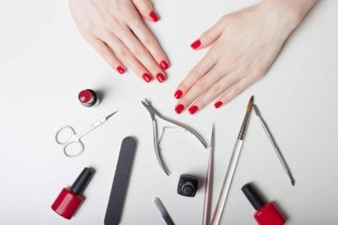 Hände mit Gelnägel und Werkzeug für Maniküre
