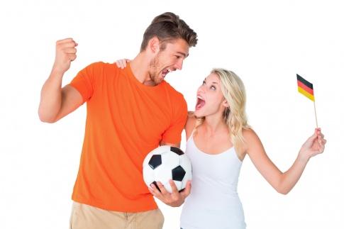 Paar in Fußball-Fanartikeln freut sich