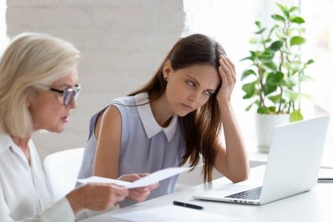 Eine Frau sitzt genervt am Tisch, während ihre Kollegin einen langweiligen Monolog hält.