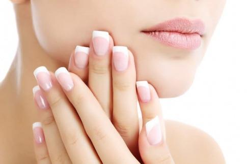 Vor dem Gesicht einer Frau sind schön gepflegte Fingernägel zu sehen