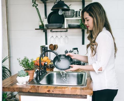 Eine Frau wäscht Geschirr mit selbst gemachtem Spülmittel