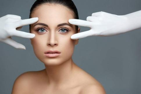 Zwei Hände in Handschuhen bei den Augen als Zeichen für Augenlidkorrektur