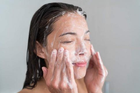 Eine Frau wäscht ihr Gesicht mit Seife
