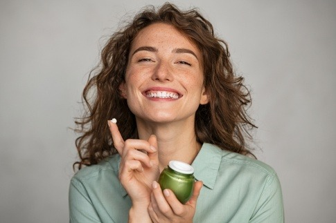 Eine Frau verwendet eine Gesichtscreme