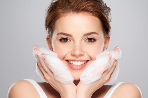 Eine Frau reinigt ihr Gesicht mit Schaum