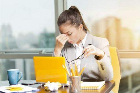 Frau am Schreibtisch reibt sich die Augen