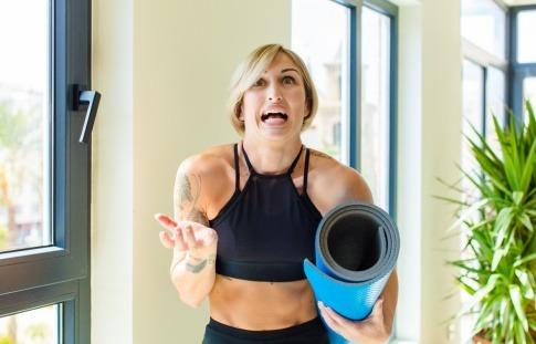 Verzweifelte oder unschlüssige Frau mit Yoga-Matte unter dem Arm.