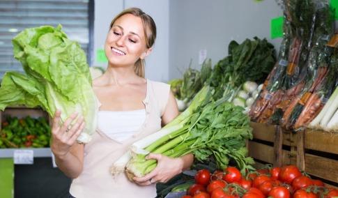 Eine Frau steht in ihrer Küche und hält diverse gesunde Lebensmittel wie Salate und anderes Gemüse in den Händen, mit denen sie gleich gesund kochen wird.