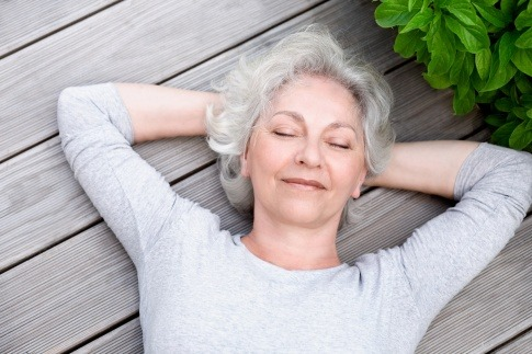 Eine ältere Frau liegt glücklich auf einem Holzboden