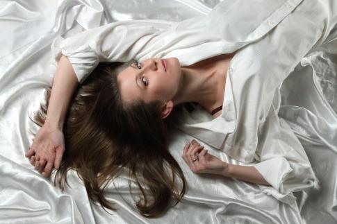 Frau auf Satinbettwäsche mit langen Haaren