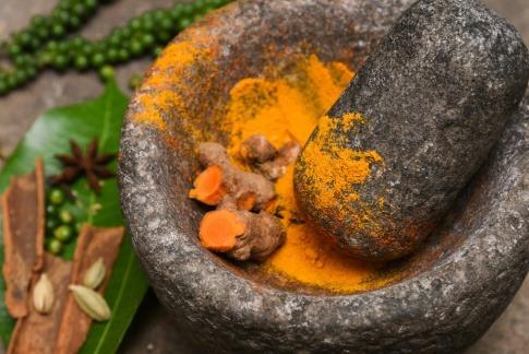Ein gelbes indisches Gewürz befindet sich in einem Mörser aus Stein