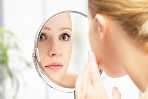 Eine Frau mit glänzender Haut schaut in den Spiegel