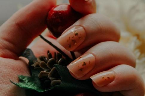 Hände mit Glass Nails halten eine Blume