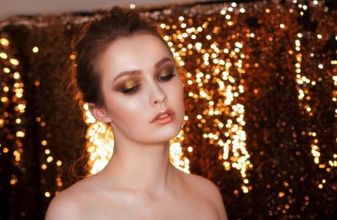 Eine Frau steht vor einem goldenen Hintergrund und trägt goldenes Glitzer-Makeup