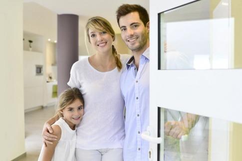 Eine glückliche Familie öffnet die Haustür