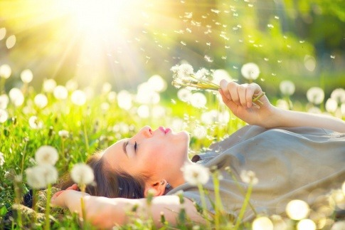 Eine Frau pustet glücklich auf eine Pusteblume