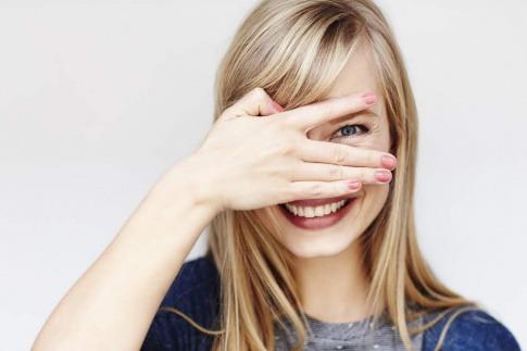 Eine Frau schaut durch ihre Finger