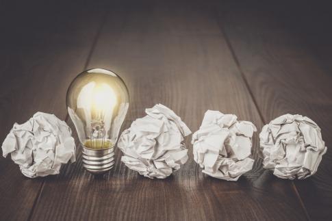 Eine Glühbirne steht zwischen drei Papierkugeln