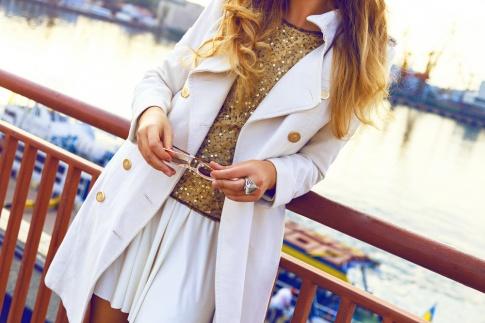 Ein Ausschnitt aus den Modetrends Herbst Winter 2018 - Close-up einer Frau an einem goldenen Herbsttag, die einen weißen Rock, ein goldenes Glitzer-Top und einen Cashmeremantel trägt.