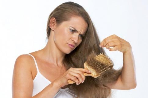 Eine Frau betrachtet ihre Haare, die langsam grau werden