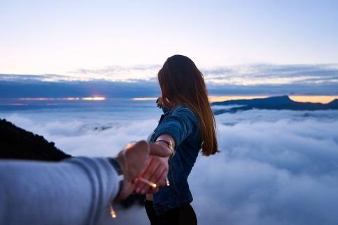 Eine Frau vor wolkigem Hintergrund will Grenzen setzen und frei sein