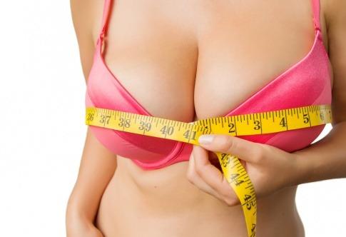 Frau misst ihre großen Brüste mit einem Maßband