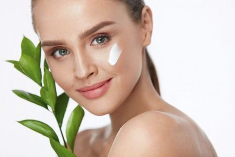 Eine Frau hat Blätter von Grünem Tee in der Hand und Kosmetik auf der Wange