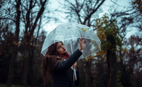 Eine Frau wirkt grundlos traurig und berührt die Innenseite eines transparenten Regenschirms an der Stelle, an der außen ein Laubblatt draufgehalten ist.