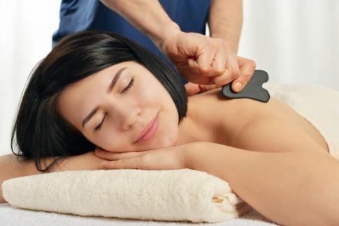 Eine Frau bekommt eine Gua Sha Massage in Wien