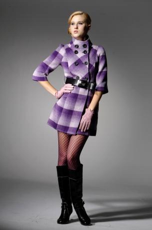 Ein weibliches Model posiert mit einem fliederfarbenen, zugeknöpften 70er Jahre Mantel vor einem neutralen Hintergrund.