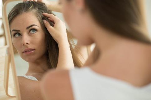 Eine Frau betrachtet ihren Haarausfall und ihre Kopfhaut